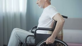 有坐在轮椅的伤残的无能为力的人,转动回到照相机 影视素材