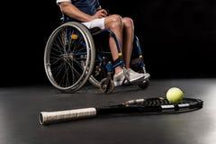 有坐在轮椅的球和残疾运动员的网球拍后边 库存照片