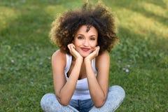 有坐在都市公园的非洲的发型的年轻黑人妇女 免版税库存照片