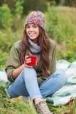 有坐在野营的杯子的微笑的少妇 免版税图库摄影