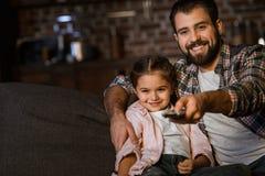 有坐在长沙发,拥抱的和观看的电视的女儿的愉快的父亲 库存图片
