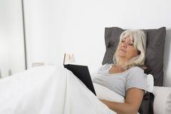 有坐在靠窗座位读书的长的头发的少妇 免版税库存照片