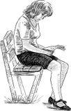 有坐在靠窗座位读书的长的头发的少妇 免版税库存图片
