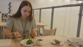 有坐在餐馆和吃素食食物的红色头发的年轻美女 健康生活方式,适当 股票视频