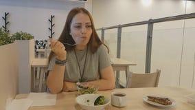 有坐在餐馆和吃素食食物的红色头发的年轻美女 健康生活方式,适当 影视素材