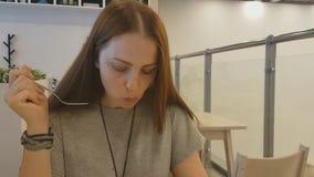 有坐在餐馆和吃素食食物的红色头发的年轻美女 健康生活方式,适当 股票录像