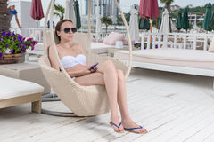 有坐在轻便折叠躺椅的手机的妇女 免版税库存图片