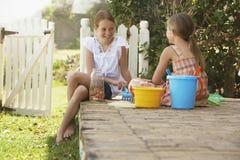 有坐在围场的海滩玩具的姐妹 图库摄影