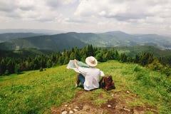 有坐在mou顶部的背包的时髦的行家旅客人 免版税库存图片