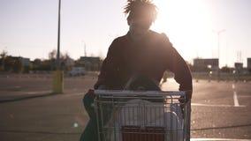 有坐在ouside停车区的购物的cort和看对他的时髦理发的美国黑人的年轻男孩 股票录像