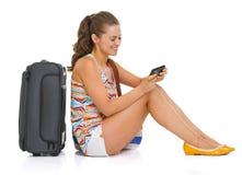 有坐地板和写sms的袋子的旅游妇女 免版税图库摄影