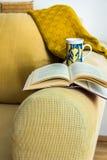 有坐垫的,被编织的毛线衣,开放书,茶杯,舒适松弛大气客厅内部黄色条绒长沙发 免版税库存照片