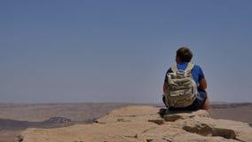 有坐峭壁` s边缘和享受沙漠视图的背包的年轻人 库存照片