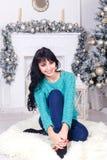 有坐户内在圣诞节的长的头发的愉快的少妇  图库摄影