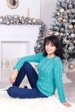 有坐户内在圣诞节的长的头发的愉快的少妇  免版税库存图片