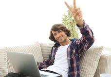 有坐沙发和显示他的手一个赢取的姿态的膝上型计算机的愉快的人 免版税库存照片