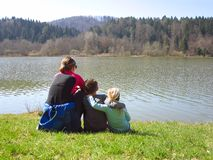 有坐由湖的孩子的母亲 免版税库存照片