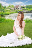 有坐由湖的花束的新娘 免版税库存照片