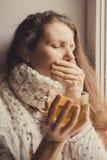 有坐由窗口的一杯茶的病的妇女 免版税库存照片
