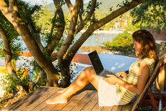 有坐的膝上型计算机的妇女在手段sunbed 库存图片