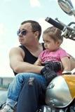 有坐自行车和调查距离的爸爸的女孩 库存图片
