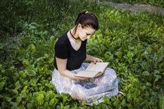 有坐草和读书的黑发的女孩 库存照片
