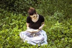 有坐草和读书的黑发的女孩 免版税图库摄影