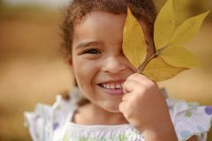 有坐草和调查照相机的黑发和棕色眼睛的一逗人喜爱的女孩,愉快和周道 图库摄影