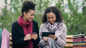有坐长凳和使用片剂计算机的纸袋的两名可爱的混合的族种妇女和信用卡为在网上 免版税库存图片
