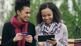 有坐长凳和使用片剂计算机的纸袋的两名可爱的混合的族种妇女和信用卡为在网上 图库摄影