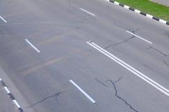 有坑洼的损坏的坏柏油路 沥青修补路面坑槽  免版税库存图片