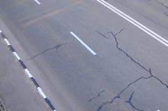 有坑洼的损坏的坏柏油路 沥青修补路面坑槽  库存照片