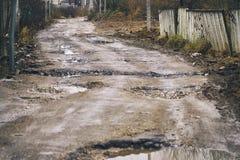 有坑的残破的土路有很多水 库存图片