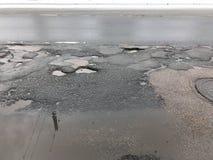 有坑洼的损坏的柏油路 库存照片