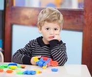 有块的不快乐的男孩在教室 库存照片