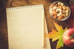 有坚果、苹果和秋叶的空白的棕色笔记本在木桌上 仍然秋天生活 免版税图库摄影