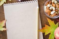 有坚果、苹果和秋叶的空白的棕色笔记本在木桌上 仍然秋天生活 库存图片