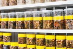 有坚果和蜂蜜的玻璃瓶子在柜台在一个市场上作为背景 免版税图库摄影