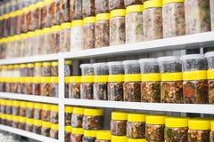有坚果和蜂蜜的玻璃瓶子在柜台在一个市场上作为背景 免版税库存照片