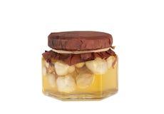 有坚果的蜂蜜瓶子 免版税库存图片