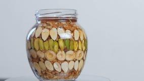 有坚果的转动的开放瓶子在蜂蜜 特写镜头侧视图 影视素材