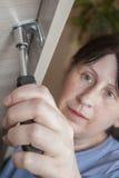 有坚果锭床工人螺丝刀的妇女手拉紧坚果,特写镜头 免版税库存照片