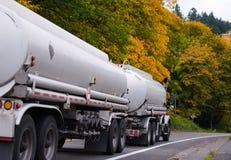 有坦克拖车的半白色卡车在秋天树路 免版税图库摄影