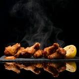 有垂度和辣调味汁的热和辣bbq鸡翼在黑石板材 库存照片