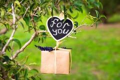 有垂悬在一个树枝的淡紫色枝杈的礼物盒,您的在夹子标签,华伦泰,婚礼,爱,浪漫概念的字法 免版税库存照片
