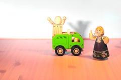 有垂悬在一辆绿色卡车的一个木玩偶和围巾的一个勇敢的母亲 免版税库存照片