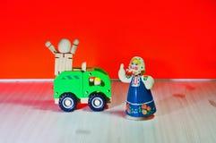 有垂悬在一辆绿色卡车的一个木玩偶和围巾的一个勇敢的母亲 免版税库存图片