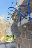 有垂悬在墙壁上的古铜色响铃的一个小灰色石房子 免版税库存照片