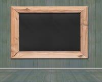 有垂悬在木墙壁上的木制框架的空白的黑板 免版税库存照片
