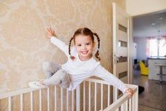 有垂悬在白色婴孩小儿床上的辫子的小女孩 免版税库存图片